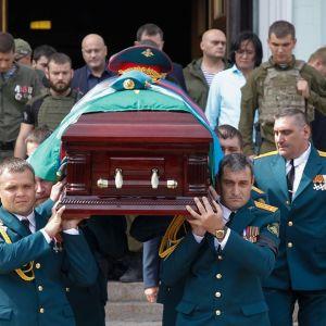 Joukko vihreisiin edustusunivormuihin pukeutuneita miehiä kantaa arkkua kirkon portailla. Arkun päällä on koppalakki ja Donetskin lippu. Taustalla näkyy miehiä maastounivormuissa.