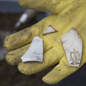 Mullan seasta löytyneitä astian palasia kämmenellä.