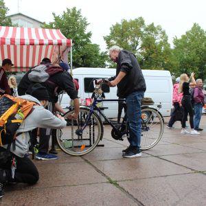 Nuoria miehiä pumppaamassa ilmaa vanhemman miehen polkupyörän etukumiin Karhulan torilla.