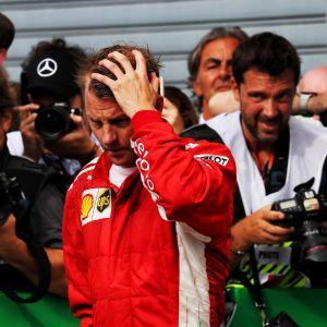 Ferrarin Kimi Räikkönen haroo hiuksiaan varikolla.