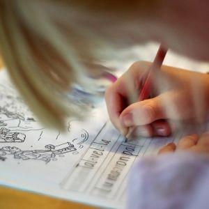 Lapsi kirjoittaa tehtävävihkoon.