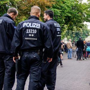 Joukko poliiseja seisoo etualalla tummansinisissä haalareissa. Kauempana väkijoukko alkaa kokoontua mielenilmaukseen.