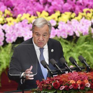 YK:n pääsihteeri Antonio Guterres puhuu, taustalla on värikkäitä kasveja.