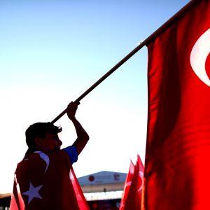 Mies heiluttaa Turkin lippua.