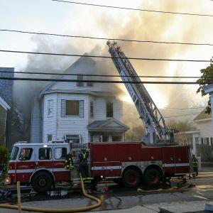 Kuvassa palava kaksikerroksinen puutalo. Paljon savua tulee rakennuksen ikkunoista.