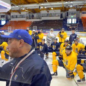 Jääkiekkojoukkue Jukureiden pelaajat seuraavat, kun päävalmentaja Pekka Mäenalusta piirtää fläppitauluun jääkiekkokaukalossa.
