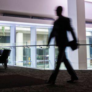 Toimistomaisema jossa työntekijä kuvattuna epäterävästi, kuvituskuva.