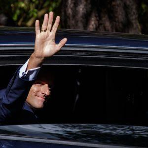 Macron vilkuttaa auton ikkunasta.