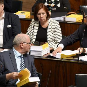Eero Heinäluoma, Sirpa Paatero ja Antti Rinne tutkivat budjettikirjaa Eduskuntasalissa.
