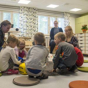 Opetusheti esikoulussa, lapset ympyrässä lattialla opettajan kanssa.