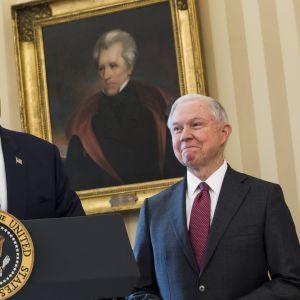 Presidentti Donald Trump pitää puhetta vasemmalla, oikealla virkavalan vannomista odottava Jeff Sessions.