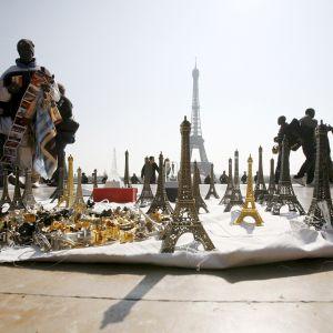 Katukauppiaat myyvät turisteille Eiffel-tornin pienoismalleja Pariisissa.
