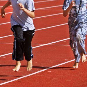 Kaksi poikaa juoksee liikuntatunnilla.