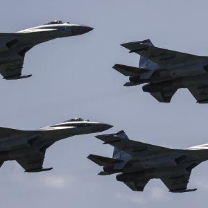Neljä hävittäjää lentää muodostelmassa vasten sinistä taivasta.