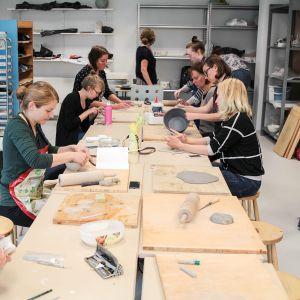 Naisia pitkän pöydän ääressä savitöitä tekemässä.
