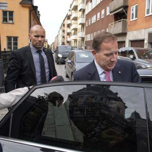 Löfven nousee mustaan autoon tukholmalaisella kadulla. Taustalla seisoo turvamies tummassa puvussa, nappikuuloke korvassaan.