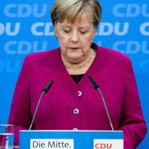 Puolikuva Angela Merkelistä violentinpunaisessa jakussa, katse alaspäin luotuna.