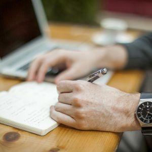 mies kirjoittaa muistivihkoon