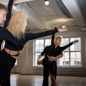 Tanssijat Jaak Vainomaa ja Tiina Tulikallio poseeraavat latinalaistanssiasuissa treenisalilla.