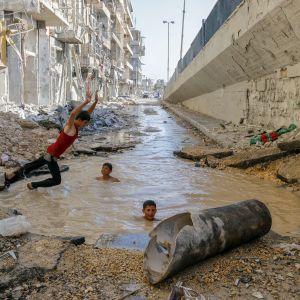 pojat leikkivät pommin repimässä kraaterissa Aleppossa