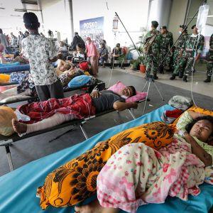 Maanjäristyksestä ja tsunamista selvinneet odottavat siirtoa eteenpäin Palun lentokentällä.