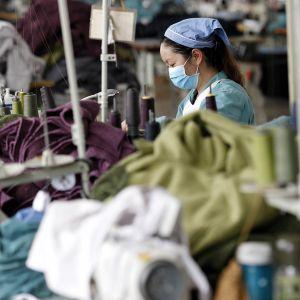 nainen ompelee vaatetehtaassa