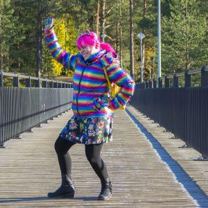 Hyvin värikkäästi pukeutunut nainen kävelysillalla.
