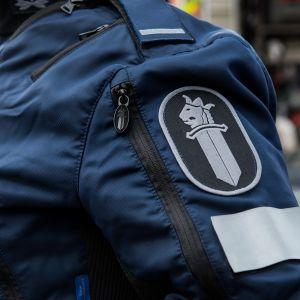 Poliisiin logo poliisi univormussa