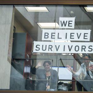 Kaksi naista senaatin toimistorakennuksen ikkunassa.