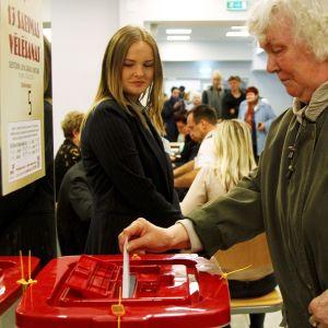 Nainen pudottaa äänestyslippua vaaliuurnaan.