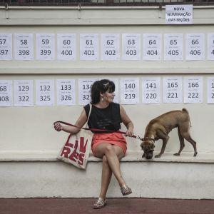 Nainen istui äänestyspaikalla Rio de Janeirossa 7. lokakuuta koiransa kanssa.