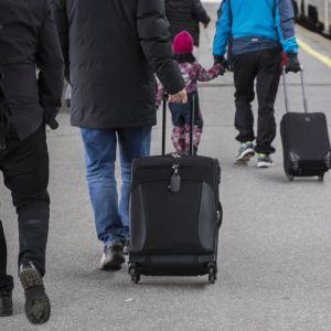 Matkustajia ja matkalaukkuja asemalaiturilla.