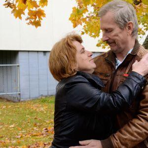 Nainen ja mies halaavat syksyisten puiden alla.