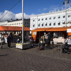 Ihmiset juovat torikahveja Helsingin Kauppatorilla