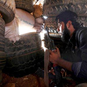 Syyrian kapinallistaistelija  tarkkailee etulinjaa autonrenkaista tehdystä suojasta.