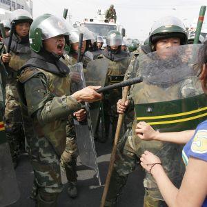 Uiguurinainen ja mellakkapoliiseja.