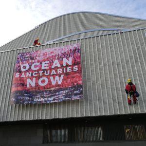 Greenpeacen mielenosoittajia Lappia-talon katolla ja seinällä 11.10.2018