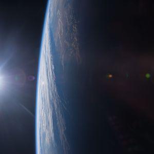 Auringonlasku kuvattuna avaruudesta. Kuvan vasemmassa laidassa on pieni kirkas aurinko ja oikealla iso maapallo.
