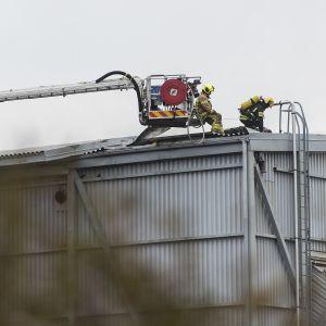 Palomiehiä rakennuksen katolla.