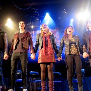 Kuusi näyttelijää käsi kädessä laulavat näyttämän kirkkaissa valoissa