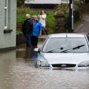 Siniharmaa Ford-auto osittain veden alla, taustalla seisoo kaksi miestä vedessä, nainen ottaa kuvaa kännykällä.