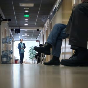 Hoitaja kävelee käytävällä, ihmisten jalkoja etualalla.