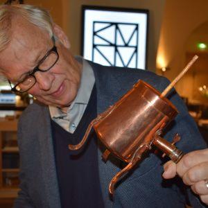 Antiikkiasiantuntija Wenzel Hagelstam tutkii kupariesinettä.