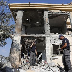 Israelin poliisi tutkii raketti-iskussa tuhoutunutta taloa Beershebassa.