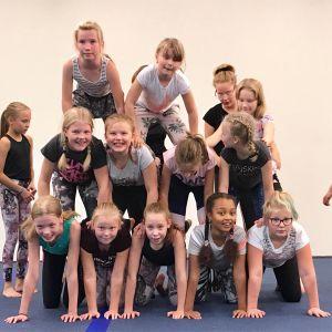 9-10-vuotiaat ovat muodostamassa pramidia, jossa ihmiset ovat kontallaan rivissä ja heidän päälleen tulee aina seuraava rivi. Tässä ihmispyramidissa on kolme kerrosta.