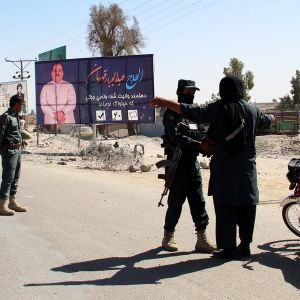 Afganistanilaiset turvallisuusviranomaiset tarkastavat ihmisiä pommi-iskun jälkeen Helmandissa Afganistanissa.