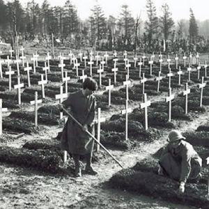 Mustavalkoinen kuva kymmenistä haudoista, kaikilla samanlainen valkoinen puuristi. Etuajalla kaksi naista tasoitaa yhden haudan kumpua.