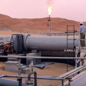 työntekijä seisoo öljyputken päällä aavikolla