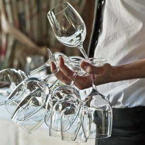 Tarjoilija viinilaseja kädessään.