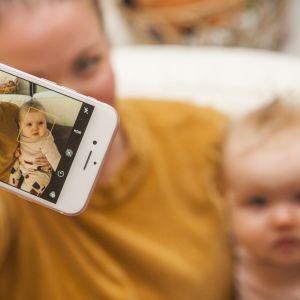 Äiti ottaa kuvaa itsestään ja vauvasta älypuhelimella.